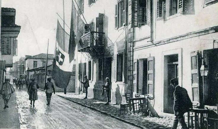 Italian soldiers in Vlorë, Albania during World War I. The tricolour flag of Italy bearing the Savoy royal shield is shown hanging alongside an Albanian flag from the balcony of the Italian prefecture headquarters.