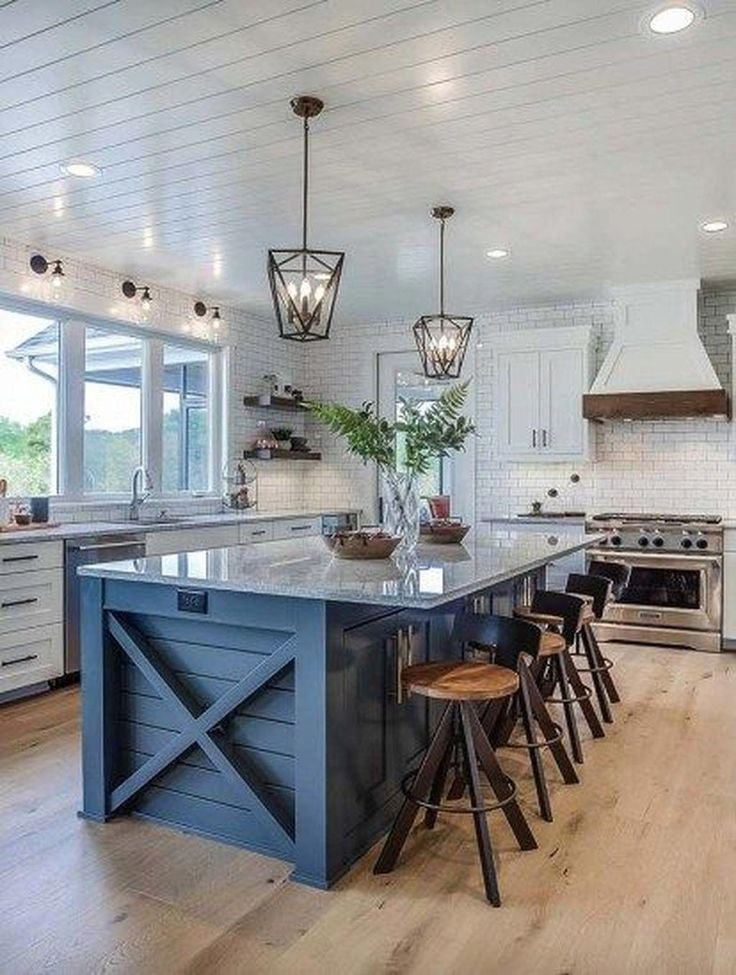 modern farmhouse kitchen with navy blue island and stools