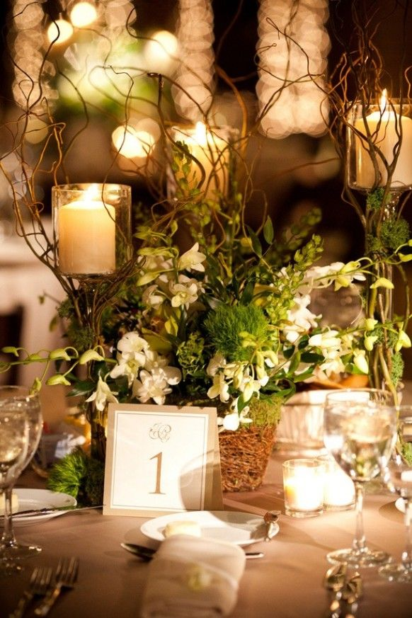 Candles and tea lights give a soft glow to indoor garden themed wedding reception table decor.