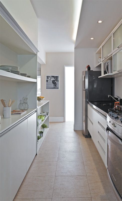 A estante com armários e prateleiras é o verso do painel para a TV.   Projeto de Renata Cáfaro.