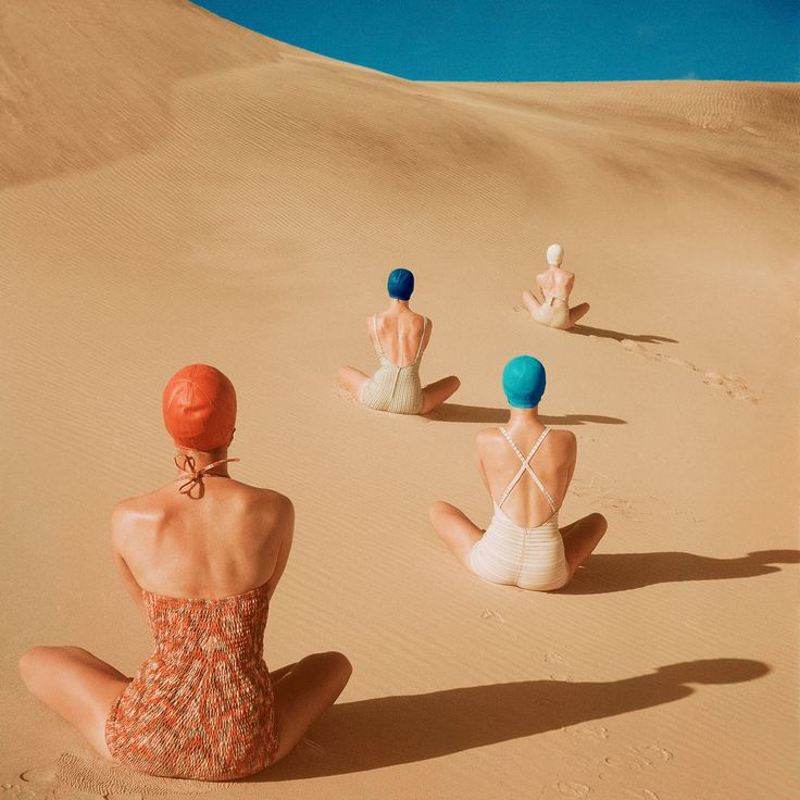 """Four models look out peacefully into a sandy abyss in """"Sun"""" by Clifford Coffin, which appeared in Vogue (June, 1949). Backs to the camera, they sport, from left: swimsuits by Cole of California, Mabs, Caltex, and Catalina - with bathing caps to match, naturally."""