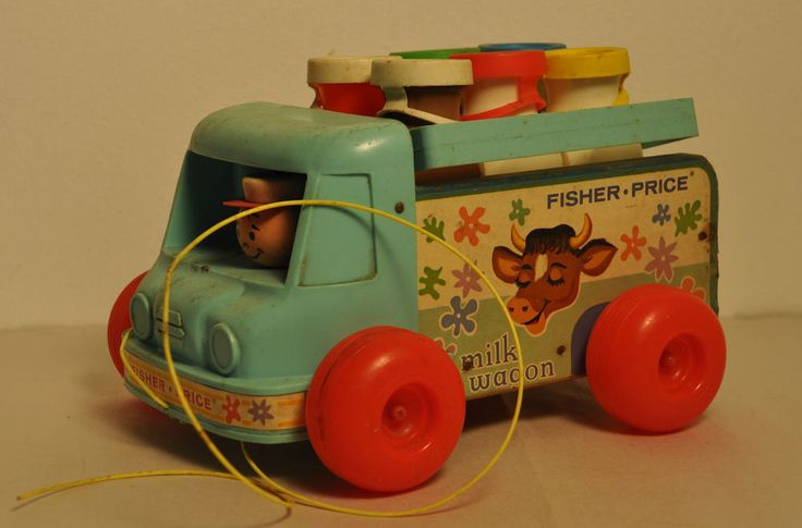 "Vintage Fisher Price 131 Milk Wagon W/Milk Bottles And Carrier 1967 - 72 #FisherPrice Turquoise milk truck with a plastic front cab and wooden truck bed and sides. The sides have a white paper lithograph of a cow's head and the words, ""Fisher-Price"" and ""Milk Wagon"". The truck has a round wooden head driver wearing a round white cap who turns to look from left to right as the truck is pulled. The truck also has a hidden bell that rings when the toy pulled."