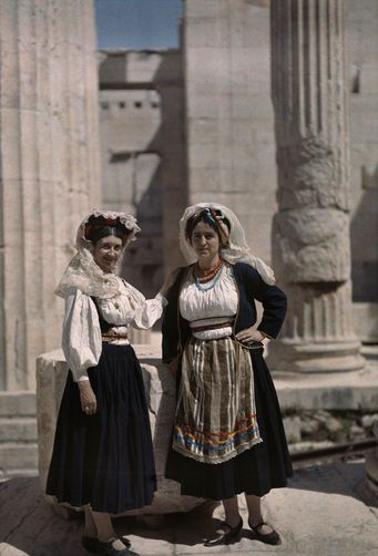 Two women stand in vestibule of Acropolis wearing costume of Corfu. Location: Acropolis, Athens, Greece.  Photographer: MAYNARD OWEN WILLIAMS/National Geographic Creative