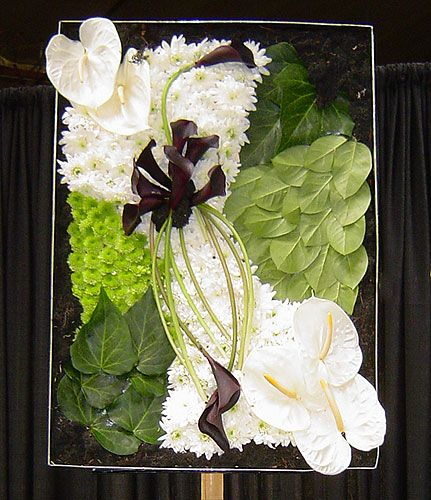 Unique floral art featuring black callas, white Anthuriums, green button chrysanthemums and a variety of foliages. Designed by Marisa Perring, AIFD.