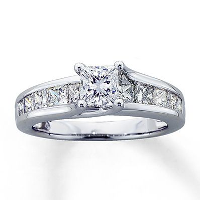 Cool A princess cut diamond graces the center of this brilliant ring and is acpanied on the sides by additional princess cut diamonds channel set into the