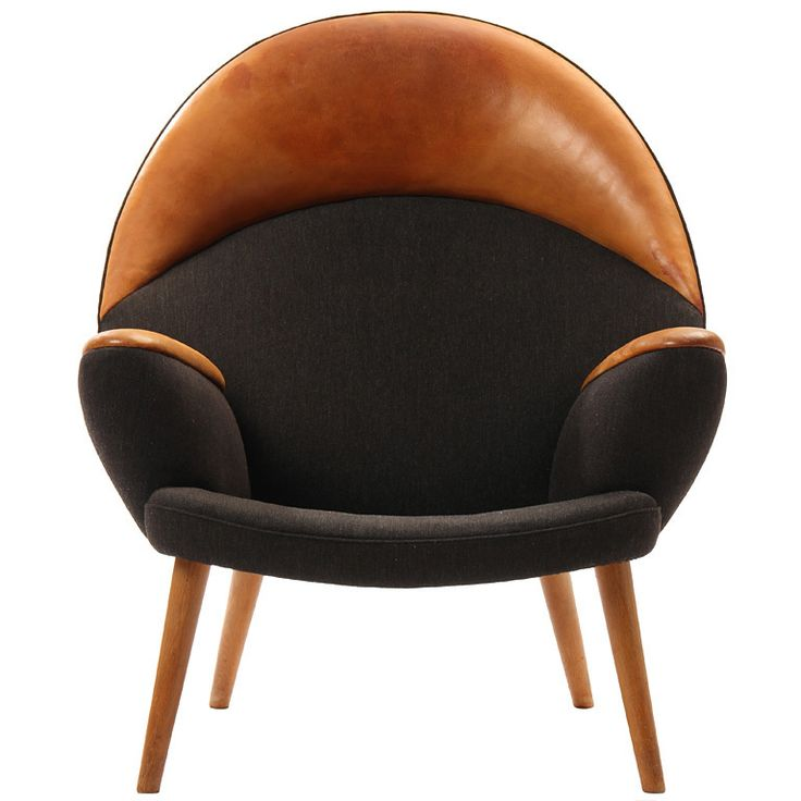the Upholstered Peacock by Hans J. Wegner  Denmark  1955  A rare lounge chair with the original charcoal wool Savak upholstered body and natural leather head and armrests on tapered oak legs. Model JH 521 design by Hans J. Wegner cabinetmaker Johannes Hansen Copenhagen.