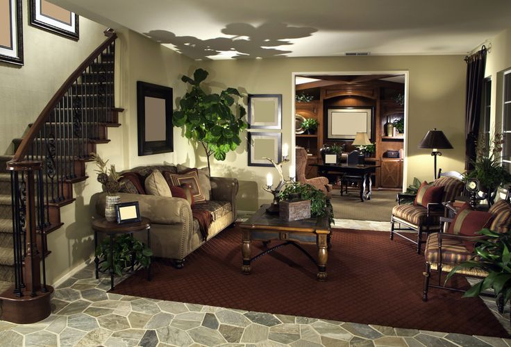 This cozy living room setup stands beneath the carved wood and wrought iron stair railing at left, with a deep burgundy rug over stone tile flooring. Large, carved wood coffee table stands between arched back sofa and twin dark wood framed chairs.