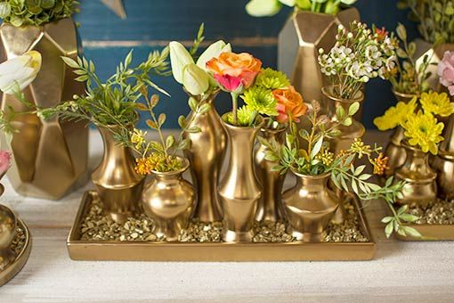 This gold toned ceramic vase cluster set on a tray
