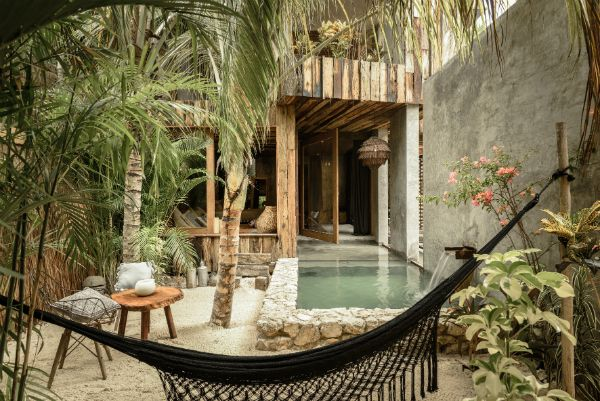 Could this be a more perfect Bohemian retreat? Hammocks, palms and a plunge pool. Natural wood look construction and simple designs.