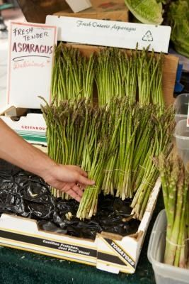 How to grow asparagus in raised beds. Asparagus is a perennial vegetable plant that can be a long-lasting, permanent addition to a home garden. This vegetable requires well-draining soil to thrive; waterlogged soil can cause the roots of the asparagus plant to rot. Growing asparagus in raised beds offers them well-draining soil, as well as being a more convenient way to plant asparagus, since it does not require that you till the soil deeply with a rotary tiller.