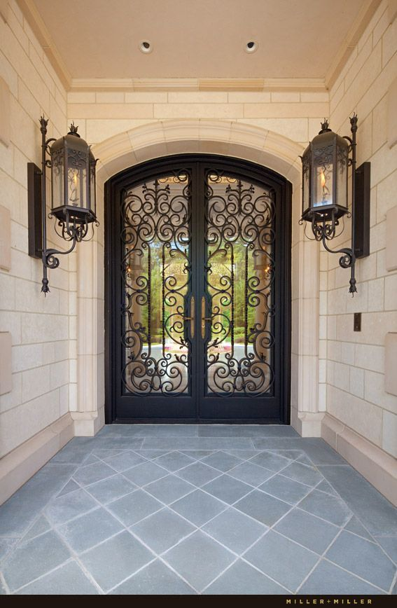 Custom ornate handmade wrought iron and glass front entry double door with custom gas lanterns. Slate tile floor and Indiana Limestone walls. See more photos at: http://www.millermillerrealestate.com/luxury-custom-home-builder-architectural-photographer.html Ryan and Sarah Miller Realtors Photography by Miller + Miller Architectural Photography