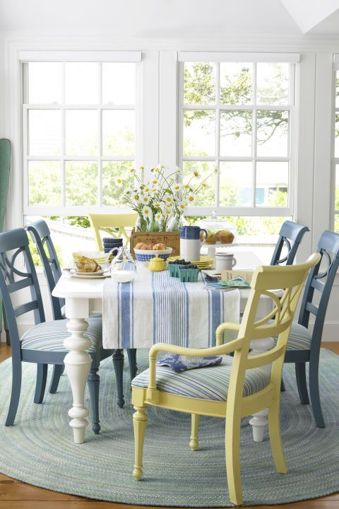 """Sunny Breakfast Nook: This breakfast nook has a beachy, barefoot quality—€""""underscored by a braided rag rug, deliberately mismatched seats, and a pair of oars leaning in one corner and painted a color similar to """"Treasure Isle"""" by Olympic. A crate full of glass bottles offers a foolproof way to arrange flowers."""