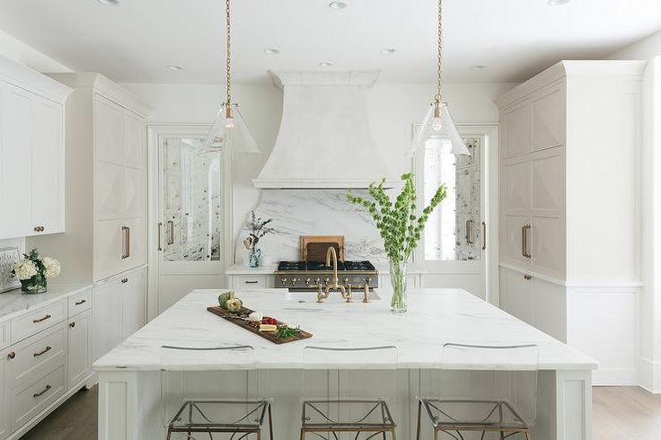 Mirrored Pantry Doors Flank A White Wood Panel French Vent Hood Fixed To A Curved Marble