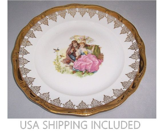 This cabinet plate glowing with gilt was made by the Gloria Fine Porcelain Manufactory, founded in 1913 and still in business in Bayreuth, a town in Bavaria in Germany. Gloria is famous for their use of the finest materials to make their porcelains. Not only is the scalloped, embossed rim heavily gilded, there is a pretty lacy design in gold that encircles the plate below the rim. In the center is a transfer of a romantic painting of a courting couple by J. C. van Hunnik, a noted Dutch…