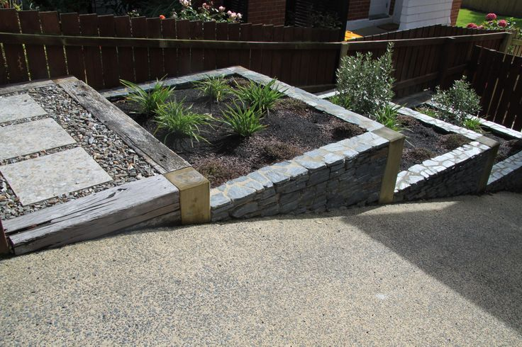 Schist and hardwood terraced gardens provide an elegant solution for this driveway edge.