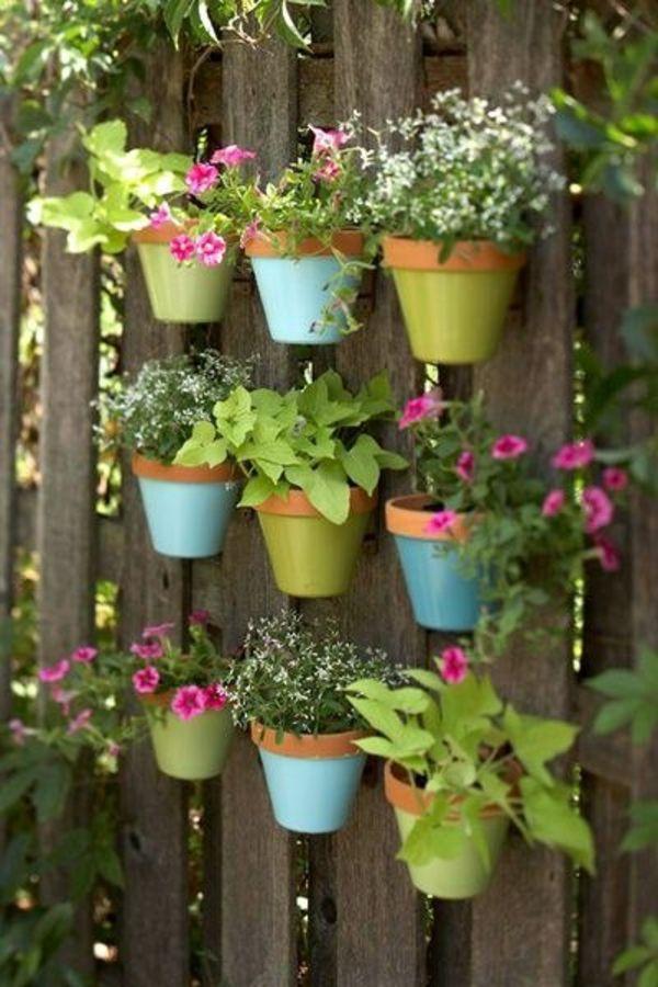 Bunte Blumentopfe Fur Kleine Pflanzen Am Gartenzaun Befestigt Garten Drau En Grun