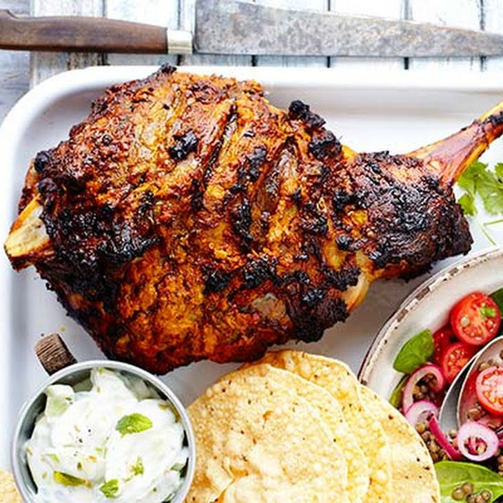 Spiced Roast Lamb Recipe Main Course with leg of lamb, whole milk yoghurt, ginger, large garlic cloves, tomatoes, lime, ground cumin, tumeric, chili flakes, fennel seeds, coriander
