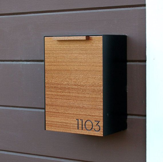 This is a Stainless Steel and Mahogany mailbox measuring 9W x12.5H x 6D. I designed this mailbox after the 1950s black mailbox that used to hang on my house. I really liked the way it functioned and it inspire me to design this modern version of it. The wood gives it some warmth while the 14ga Stainless Steel cover protects and creates a sturdy shell. It easily attaches to an exterior wall by two keyhole brackets located on the back of the mailbox. These brackets hang from two round head…