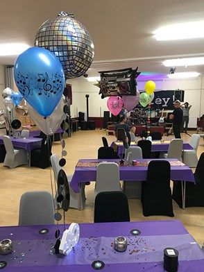 We had 70's, 80's and 90's tables in a local village hall. With Black & silver chair covers, purple table runners and a wide range of colourful balloons.