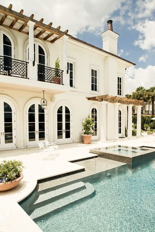 Beautiful two story white mansion with shuttered doors + windows. Poolside.