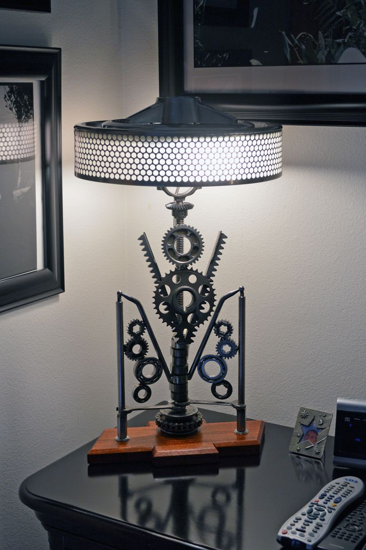 """This lamp was inspired by an Art Deco era gate, seen in NYC at the Cooper-Hewitt museum. The gate had gears on the sides. This uses transmission gears and bearings, as well as timing gears to make the V8 element, which is bolted to a bracket and stands out in front of the main lamp about and inch and a half. It is removable and I've made 2 other pieces that can go on the bracket. Since the hubcap is a Chevy piece the base is designed as a Chevy emblem, from 1"""" thick Mahogany."""