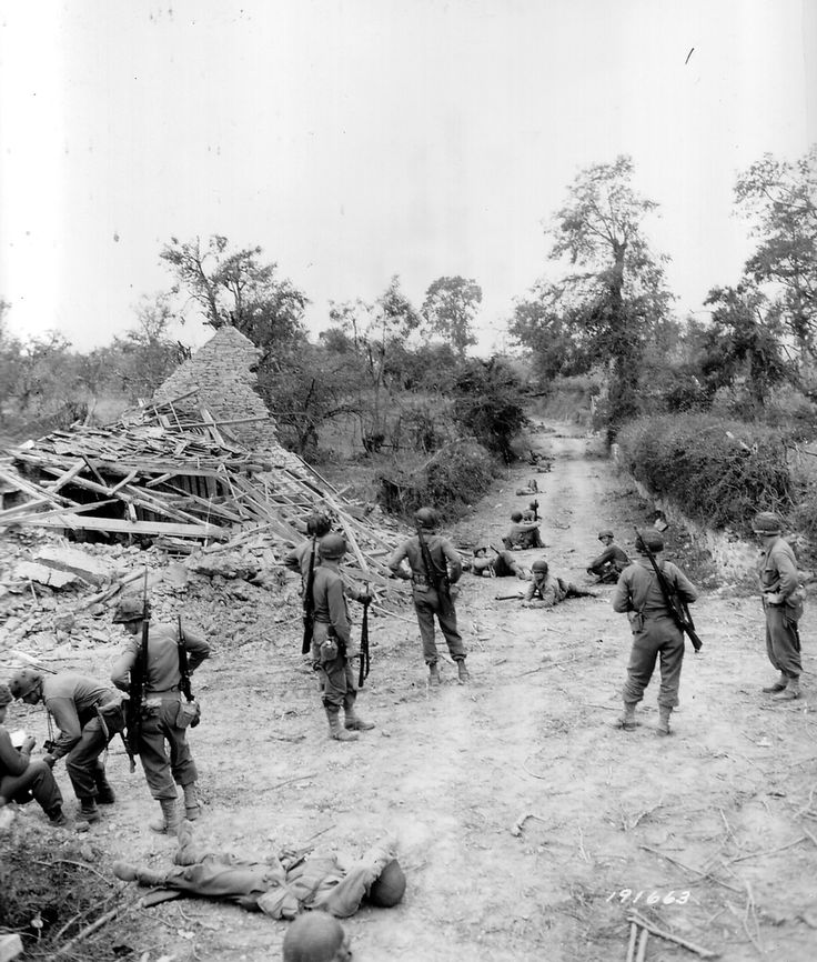 29th Infantry Division soldiers lay low along Route D191 heading toward Saint-Lô, while a map or message is read (lower left corner). 18 july 1944