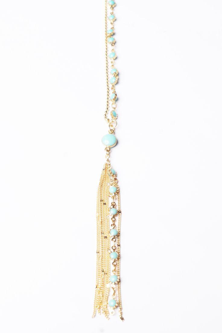 Collar con recubrimiento en  oro con cuentas de turquesa y colgando un dije en flecos de cadena doradas
