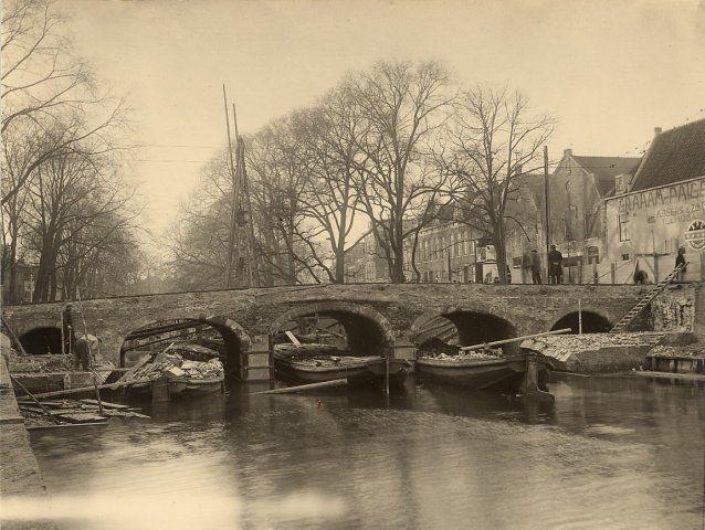 De sloop van de oude Grote Houtbrug, over de Gasthuissingel tussen de Grote Houtstraat en het Houtplein, ziende naar het westen. NB. tijdens de sloop van de oude Grote Houtbrug, kwam de zeer oude Houtbrug van de Grote Houtpoort tevoorschijn, aan deze oude brug heeft men in ca. 1824 aan weerszijde een grote boog gebouwd waardoor de brug in breedte toenam, 1929