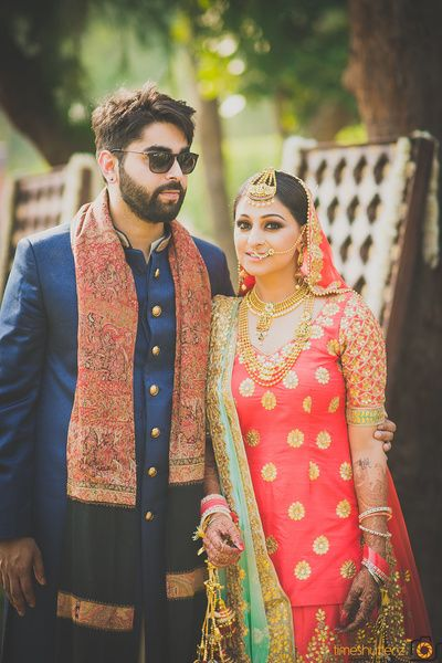 Candid Couple Shot - Bride in a Coral Lehenga with Green Net Dupatta and the Groom in a Navy Blue Sherwani with a Black Shawl | WedMeGood #wedmegood #indianbride #indianwedding #bridal #sherwani #candidcouple #candidcoupleshot