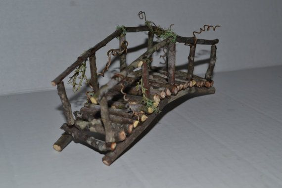 Fairy Garden Bridge  This cute little bridge is the perfect addition to your fairy garden, doll house, or terrarium. The bridge measures 6.75 inches long by 2.5 inches tall. and is made with twigs, live reindeer moss, and dried vines. This item is held together by an adhesive used by professional miniature craftsmen. The adhesive used is water-resistant, but exposure to the elements outside will limit the life expectancy of the piece. While I did hide much of the glue, there many be a few…