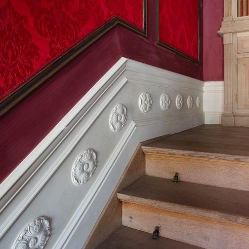 Yüksek süpürgelikler, çıtalar, dekor objeleri ve duvar kağıdı ile oluşturulan klasik mekan tasarımı..