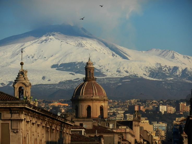 A view of a smoking Mount Etna covered by snow