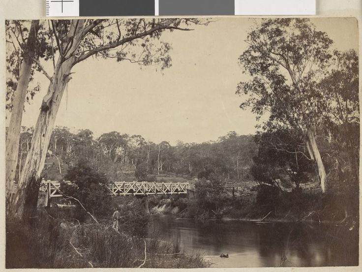 Photographic print of the Yarra River, with wooden bridge over water and bushland behind. A man stands pole fishing on bank l.l. 1867.