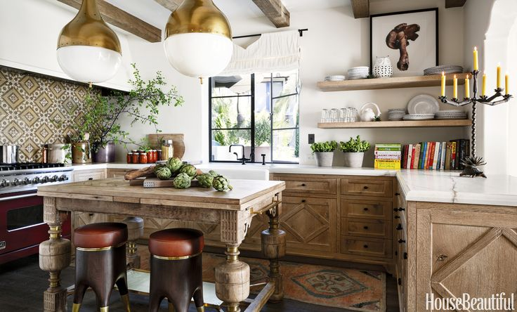 Bold shapes dramatize the kitchen, where Eccola pendants float above a massive circa-1890 Flemish oak table (Martin added brass accents). Playful molar-shaped stools by Blackman Cruz are clad in a leather by Holly Hunt. The backsplash behind the Viking range is made of antique Tunisian tiles.  Rohl sink with Sonoma Forge fittings.   - HouseBeautiful.com