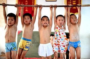 Children strain to hold on to the bar as long as possible — Gymnastics summer camp in Bozhou, Anhui province, China. Children with promise are selected to attend, and their families hope training will not only benefit their children physically but also increase 'willpower', according to China News Service. Photo by ChinaFotoPress