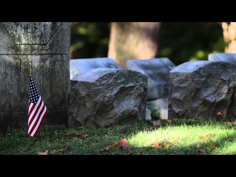 HD stock video footage of a cemetery with a memorial flag.