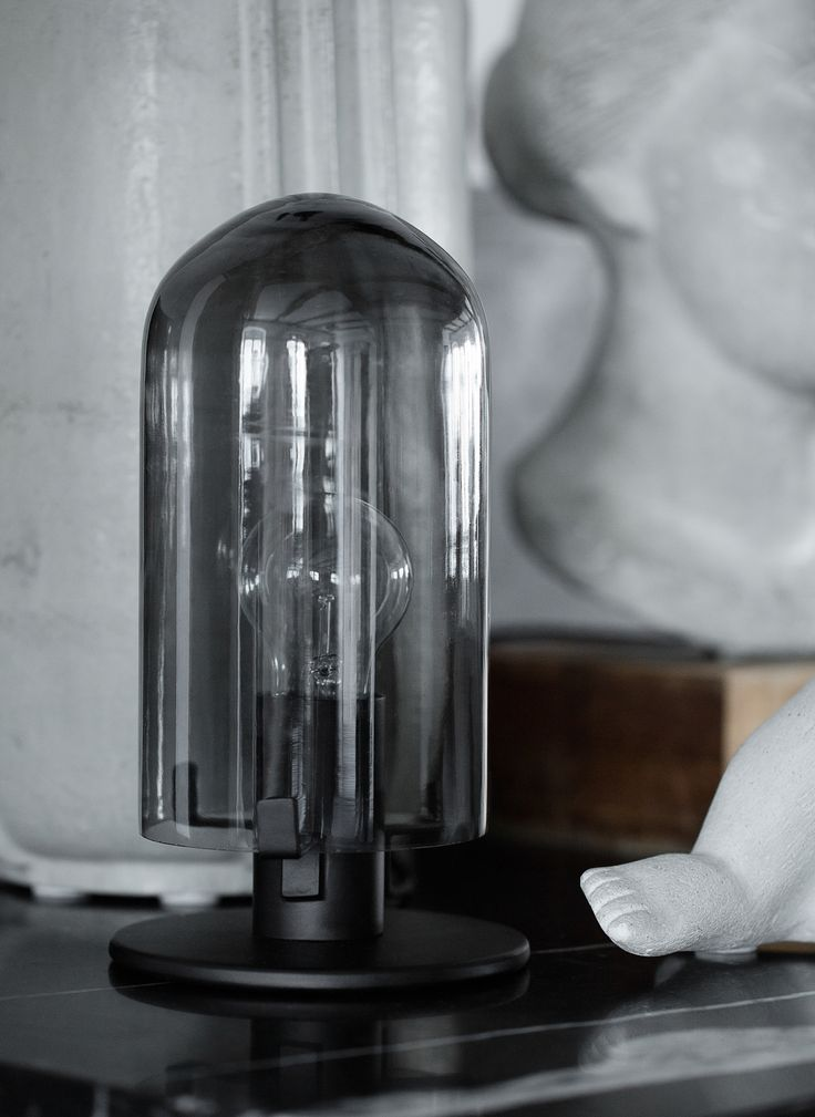 In Denmark, where winters are long and cold, creating a warm atmosphere is a way of life. This small lamp creates Danish Hygge with its smoked glass dome. Looking back at classical design from the 50s and 60s Lasse Storm Jørgensen have designed this small table lamp for Klassik Studio. The lamp is designed to fit perfectly on the desk, shelf or night stand in the home.