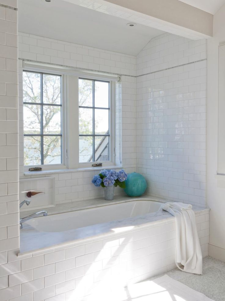 """In a waterfront property on the far eastern edge of Shelter Island, N.Y., architect Jack Wettling used a palette of crisp white accented with sea blue to create a relaxing master bathroom. """"The colors draw in the views from the picturesque Coecles Harbor,"""" he says. A judicious use of high-end stone — in the marble tub surround and a narrow marble border on the wall — lends a luxe look without breaking the bank."""