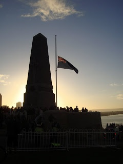 Dawn Service at the King's Park memorial in Perth, WA, 2011- sun rising behind the memorial, flag at half mast.
