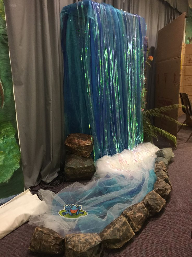 Side view of stage waterfall feature. Glittered, colored tulle made for look with shiny tinsel (actually a backdrop for a Photo Booth...found at Walmart). Lined with paper rocks.