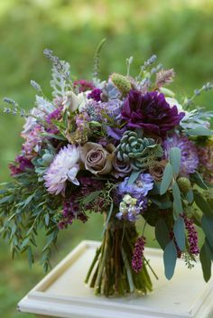 Plum and lavender bridal bouquet featuring dahlias, roses, succulents, and lots…
