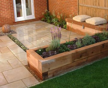 Mark Langford Garden Design. Sandstone sphere, thyme dry rill, built in storage bench, raised sleeper beds, sawn sandstone paving.