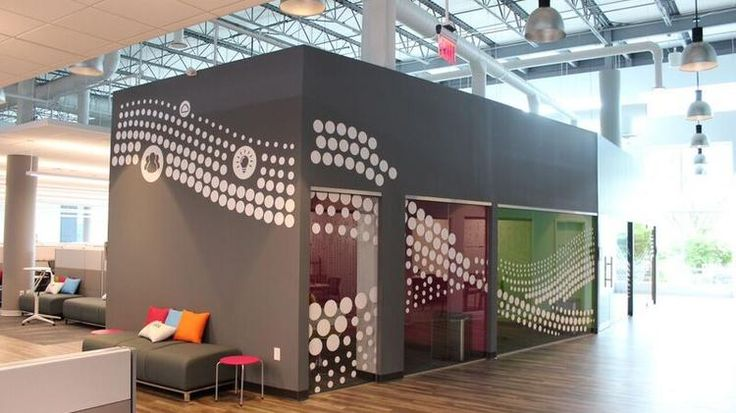 This brightly colored office with high ceilings was designed specifically by the company's owners to create a space with brand reflective paint and collaborative rooms.