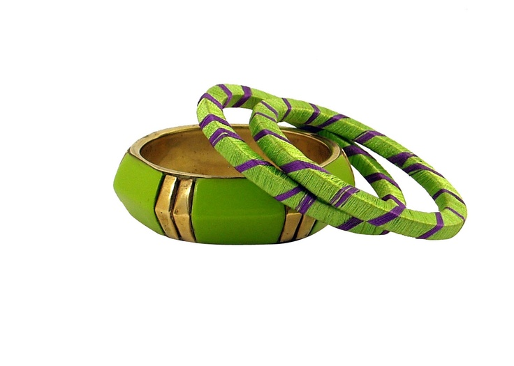 Gorgeous green and violet make this set of three bangles absolutely stunning. The wide band with shiny gold stations all hand made with raised center is a perfect bangle. A pair of bangles draped in green and violet pure silk thread. The silk threads have a classy sheen and very comfortable on the wrist.