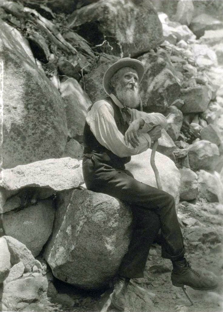 John Muir with a walking stick, in the mountains.