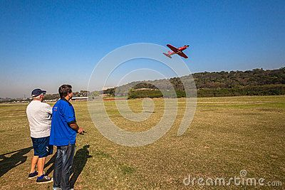 Mature males with their RC model aircraft planes at Cato Manor model flying club in Durban South-Africa. Photo image of large model plane flying pass pilot controller.