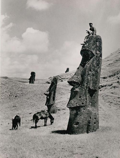 Man atop a moai (lava stone effigy) on the slope of a volcano, Easter Island (Rapa Nui), 1936, photo by Hermane Martini. (Smithsonian)