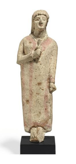 Cypriot limestone Kore, Archaic period, early 6th century B.C.  Standing with her feet together, her left arm straight at her side, her right arm bent acutely, holding an attribute, possibly a flower, in her right hand against her chest, wearing a long straight robe with red detail, and a beaded necklace with a central pendant, her hair pulled back, adorned with a red stephane, her face with bulging almond-shaped eyes and a small smiling red mouth, 28.7 cm high. Private collection
