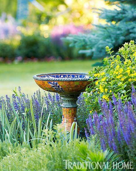 A birdbath invites friends to this lovely garden - Traditional Home® / Photo: Peter Krumhardt / Garden design: Liz & Peggy Olsen