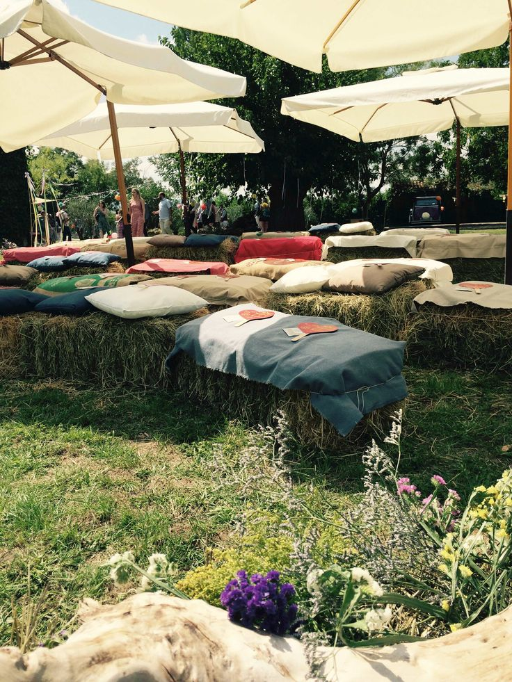 Hay bales arrangement with cushions and colored fabric for an outdoor summer wedding.
